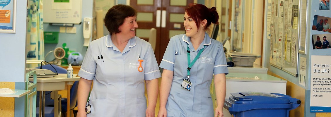 Two nurses walking and talking on a ward