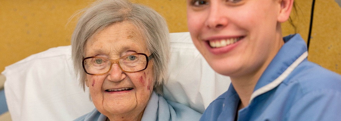 Image of an elderly patient, sat next to a smiling nurse in blue tunic.