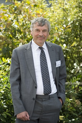 Image of Professor Ian Hall in grey suit with white tie. Stood in front of green plants.